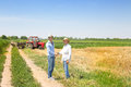 Agribusiness deal farmer and businessman shaking hands on wheat field Stock Photo