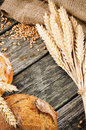 Agricultural frame with bread and wheat on wooden background Royalty Free Stock Photos