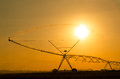Agricultural irrigation system on the wheat field at sunset Stock Images