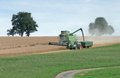 Agricultural scenery showing green harvester edge crop field harvesting summer time southern germany Stock Photo