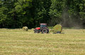 Agricultural tractor on hayfield mower Stock Photo