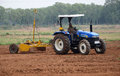 A agriculture landscaped and a tractor cultivating in the field Royalty Free Stock Images