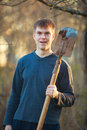 Agronomist handsome strong man with shovel on background of flo Royalty Free Stock Photo