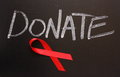 Aids awareness donate red ribbon on a blackboard under the word Stock Photos