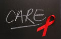 Aids awareness ribbon care red on a blackboard next to the word Stock Photos