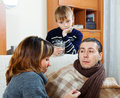 Ailing man surrounded by caring family men at home focus on Royalty Free Stock Images