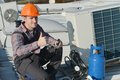 Air conditioning repairman working on a compressor and giving a thumbsup model is actual electrician Stock Photography