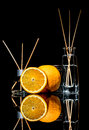 Air fresheners with orange fruits scent in a beautiful glass jars with sticks and whole orange and a slice of orange Royalty Free Stock Photo