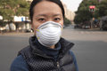 Air pollution female asian wearing a protective face mask on a city street with Royalty Free Stock Image
