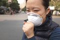 Air pollution female asian wearing a protective face mask on a city street with Stock Photo