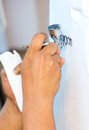 Airbrush gun sprays paint onto white cloth Royalty Free Stock Image