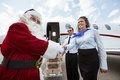 Airhostess och pilot welcoming santa against Royaltyfri Foto