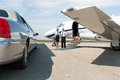 Airhostess and pilot standing neat limousine and private jet at airport terminal Stock Images