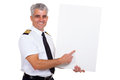 Airline captain pointing handsome middle aged airlline at blank white board over white background Stock Photo