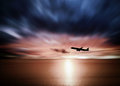 Airline flying in the sky at night beautiful colored sunset over sea Stock Images