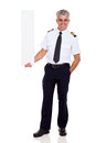 Airline pilot captain middle aged holding vertical blank banner on white background Royalty Free Stock Photo