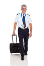 Airline pilot walking smiling senior with briefcase on white background Royalty Free Stock Photo