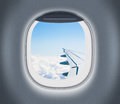 Airplane or aeroplane window with wing and cloudy sky behind Royalty Free Stock Photo