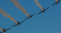 Airplane outline air show team smoke trail Synchronized Royalty Free Stock Photo
