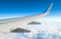 Airplane in clouds above earth wing aircraft altitude during flight Stock Image