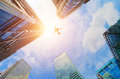 Airplane flying over modern business skyscrapers. Transport, travel. Royalty Free Stock Photo