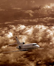Airplane flying in the sky over stormy clouds Stock Photo