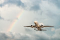 Airplane flying in sky with rainbow Royalty Free Stock Photo