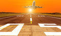 Airplane flying take off from runway on sunset Royalty Free Stock Photo