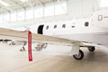 Airplane in hangar with remove before flight labels in red warning safety Stock Photos