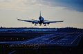 Airplane landing nightime commercial airliner is Royalty Free Stock Images