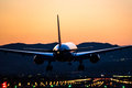 Airplane landing to the airport at dusk Royalty Free Stock Photo