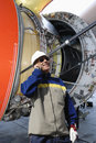 Airplane mechanic with large jet engine turbine Royalty Free Stock Photo