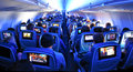 Airplane Passengers, Seats and TV screens Royalty Free Stock Photo