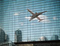 Airplane are reflected on the glass curtain wall modern building with reflection abstract cityscape Stock Photography