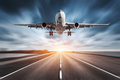 Airplane and road with motion blur effect at sunset. Royalty Free Stock Photo