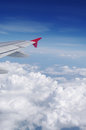 Airplane's wing in blue sky over clouds Royalty Free Stock Photo