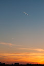 An airplane at sunset over a city flying area Royalty Free Stock Photo