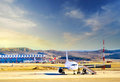 Airplane at the terminal gate Modern international airport at sunset Royalty Free Stock Photo