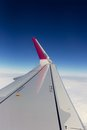 Airplane window seat view over wing whilst flying from a brand new looking the left above the clouds on holiday vacation Stock Photo