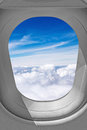 Airplane window view through sky over the clouds Royalty Free Stock Photo