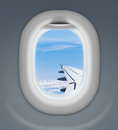 Airplane window with wing and cloudy sky behind Stock Photo