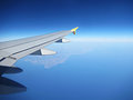 Airplane wing in the air with the continent and sea in the distance Stock Images