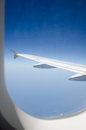 Airplane wing and blue sky through the window. Royalty Free Stock Photo