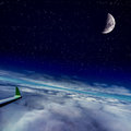 Airplane wing on flight over cloud and the moon night scene starry sky night clouds Royalty Free Stock Photo
