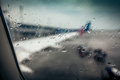 Airplane wing through passenger window with rain drops
