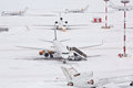 Airplanes and serving machinery on snowy airfield Royalty Free Stock Photography
