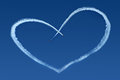 Airplanes skywriting a heart on blue sky Royalty Free Stock Image