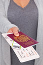 Airport check in a female handing over her passport and tickets at the tickets and labels are mock ups and all details are Royalty Free Stock Photo