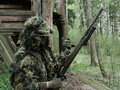 Airsoft player with ghillie suit and sniper rifle Stock Images