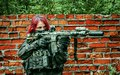 Airsoft red-hair woman in uniform with machine gun beside brick wall. Soldier aims at the sight on the street Royalty Free Stock Photo